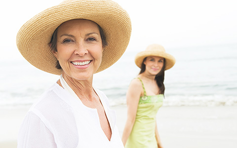 senior mom and her daughter smiling for the camera at the beach