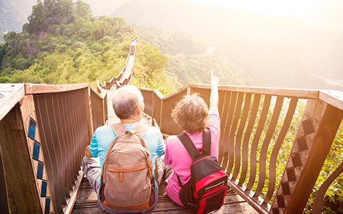 senior couple sitting on a bridge overlooking beautiful scenery