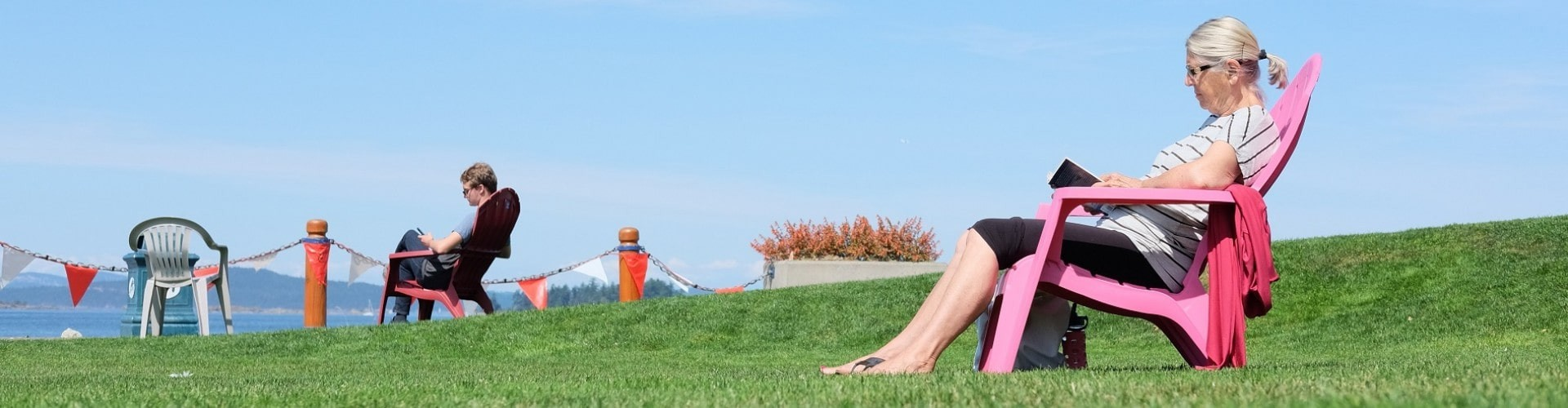 senior woman sitting on a chair on grass overlooking the ocean